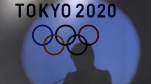 Shadow of of Tokyo governor Yuriko Koike is seen on the logo of Tokyo 2020 Olympic games during the Olympic and Paralympic flag-raising ceremony at Tokyo Metropolitan Government Building in Tokyo